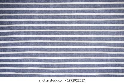 Dark blue and white stripes fabric background.