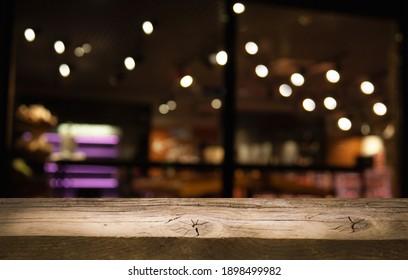 dark blurred background with empty table top, cafe restaurants windows.