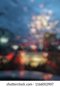 Dark blurred defocused colorful heart shape bokeh from raindrops on car glass with lighting of traffic on night time for abstract background.