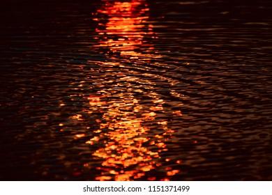 Dark blurry sunlight reflection in the water waves of a lake unique photo