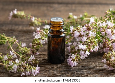 A dark bottle of essential oil with fresh blooming thyme  twigs