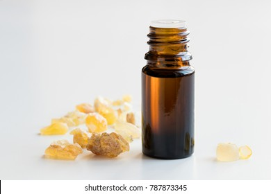 A dark bottle of frankincense essential oil with frankincense resin on a white background