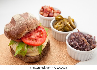 Dark bread cheeseburger with cheese tomato and aligned side servings of bacon onion cucumber