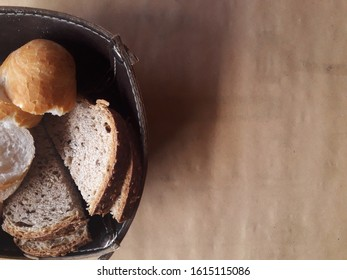 Dark bread with seeds and with a piece of bread.  Paper texture. Space copy.