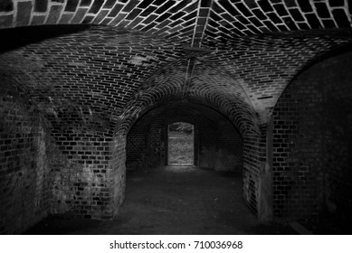 Dark brick tunnel of the catacomb with arched entrance view to the darkness of the old building