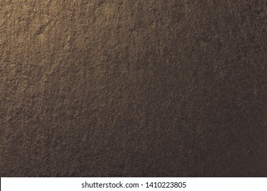 Dark bronze background of natural slate. Texture of brown stone closeup. Graphite golden backdrop macro