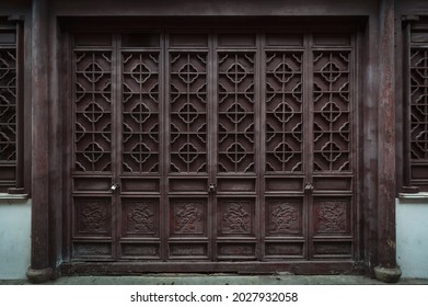 The dark brown ancient wooden door panel built in traditional Chinese architectural style and pattern at the main entrance to an old house in China