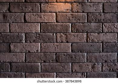 Dark brown brick wall with tungsten lighting