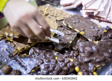 Dark and brown chocolate with nuts (almonds and hazelnuts). Seller (suman hand) picks some slices for sale. Extremely tasty and delicious desserts. Sweets full with sugar. Unhealthy food diet.