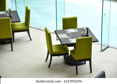 Dark brown dining table with light green chair Located in the hotel restaurant.