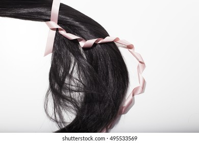 Dark brown hair pony tail with pink ribbon unrolling. Unraveling hair