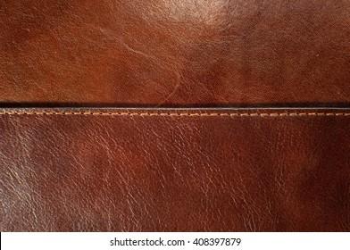 Dark brown leather texture with seam.
