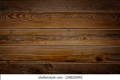 Dark brown reclaimed wood surface with aged boards lined up. Wooden planks on a wall or floor with grain and texture. Neutral stained vintage wood background.