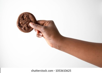 Dark brown skin African American hand and arm holding delicious cookies Chocolate biscuits isolated on white background for diet healthy eating weight loss concept