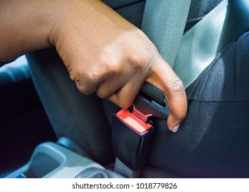 Dark brown skin African woman hand buckling safety belt in the car for automobile accident safety concept