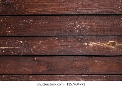 Dark brown stripped washed out wooden planks with scratches as texture. Abstract natural background