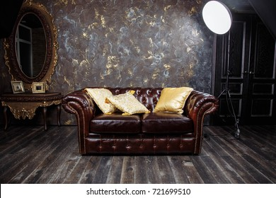 Dark brown vintage beautiful luxurious sofa interior with gray concrete texture wall in room.