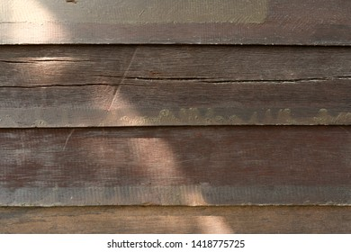 Dark brown wood slat texture background with sunrays and shadows - Wooden fence backdrop with rough surface cracks and sunlight
