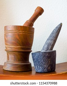 A dark brown wooden and gray stone Mortar and Pestle spice, herb and pill crusher set