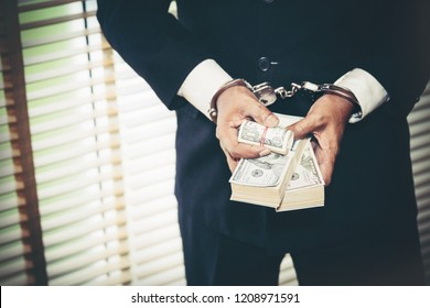 Dark business concept : Handcuffs arrested, male businessmen charged with carrying illegal counterfeit dollars.