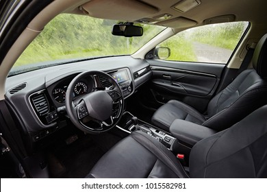 Dark car Interior - steering wheel, shift lever and dashboard. Car modern  inside. Front view on a background of nature in the rain.