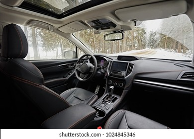 Dark car interior - steering wheel, shift lever and dashboard. Car modern SUV inside. Side view. Sunroof