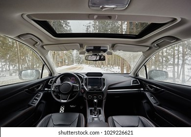 Dark car interior - steering wheel, shift lever and dashboard. Car modern SUV inside. Front view. Sunroof
