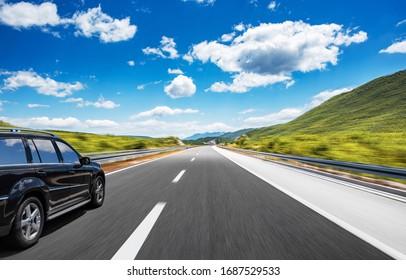 Dark car on a freeway in a beautiful area.