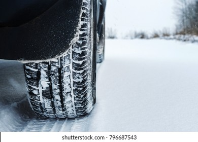 Dark car on a snowy road on a winter trip close-up of a tire protector, concept of danger on the roads in weather conditions while traveling