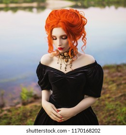 Dark carnival attire. Enigmatical witch woman with pale skin and red hair in black mystical gown and renaissance bracelet on hand pronounces spell. Enigmatical outfit for carnival. Witch spell