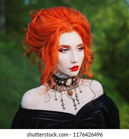 Dark carnival attire. Vampire woman with pale skin and red hair in black edwardian gown and renaissance bracelet on hand. Pale girl vampire with red lips. Gothic look. Edwardian outfit for carnival.