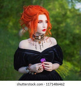 Dark carnival attire. Witch woman with pale skin and red hair in black fairytale gown and renaissance bracelet on hand pronounces spell. Gothic look. Fairytale outfit for carnival. Witch spell