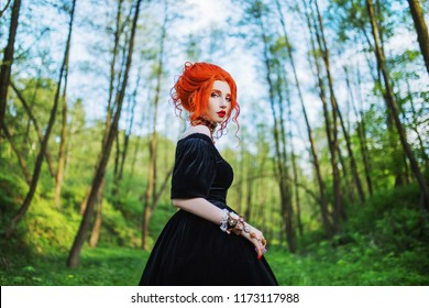 Dark carnival attire. Witch woman with pale skin and red hair in black mystical gown. Dark look. Mystical outfit for carnival. Witch spell