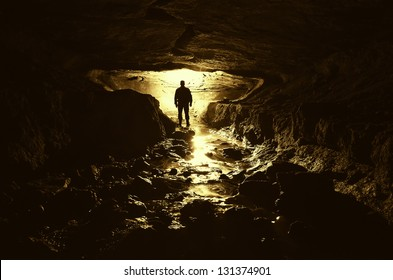 dark cave with man silhouette and water