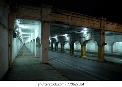 Dark Chicago city alley industrial train bridge underpass at night.