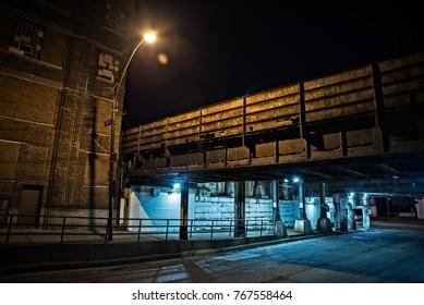 Dark Chicago city street with an industrial urban train bridge underpass at night.