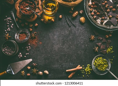 Dark chocolate background for confectionery or patisserie with broken crushed chocolate pieces , cocoa powder , nuts, cocoa beans, spices, spirits and vintage kitchen utensils, top view, frame