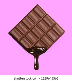 Dark chocolate bar and melted brewing drop on pink background.