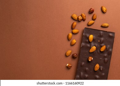 Dark chocolate bar with roasted almonds scattered around on brown background