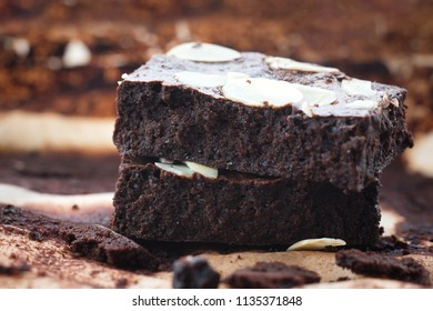 Dark chocolate brownies with almond topping, close up shot.