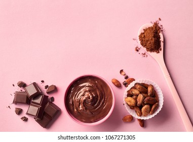 Dark chocolate, cacao powder and beans on pink background. Top view