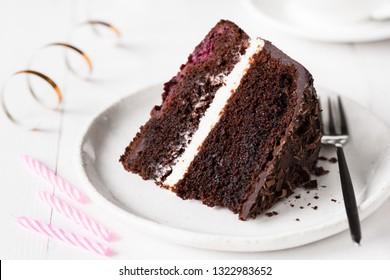 Dark chocolate cake, birthday cake on white plate. Closeup view