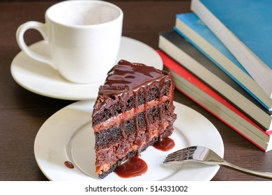 Dark chocolate cakes in white dish with fork and books