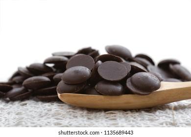 Dark chocolate chip on wooden spoon.
