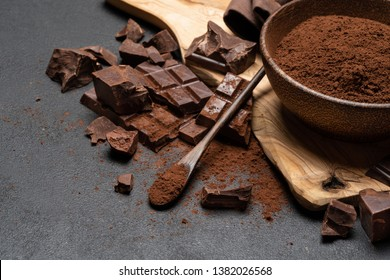 Dark Chocolate chunks and cocoa powder in wooden bowl on dark concrete background