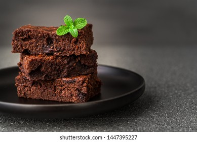 Dark chocolate and cocoa brownie fudge cakes dessert with mint against black and grey stone background