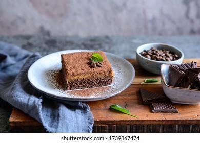 Dessert de chocolat noir garni de crème de café et arrosé de poudre de cacao sur une plaque de céramique