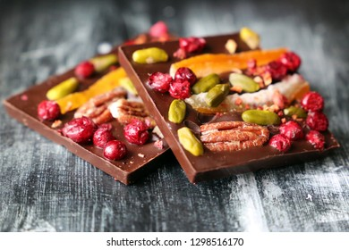 Dark chocolate with dried cranberries, citrus fruit and nuts. Tasty dessert on vintage wooden table