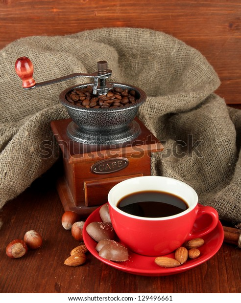Dark chocolate, hot drink and coffee mill on wooden background