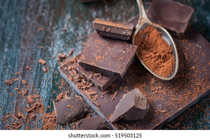 dark chocolate over wooden background, selective focus
